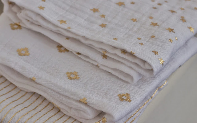 3 white muslins folded up with a different pattern in gold metallic on each one (stripes, diamonds and stars)