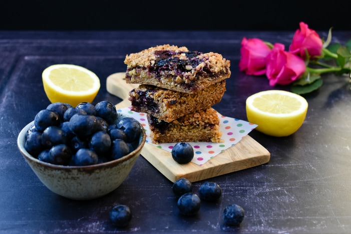 A stack of blueberry and lemon oaty bars on a wooden board with blueberries and lemon halves.