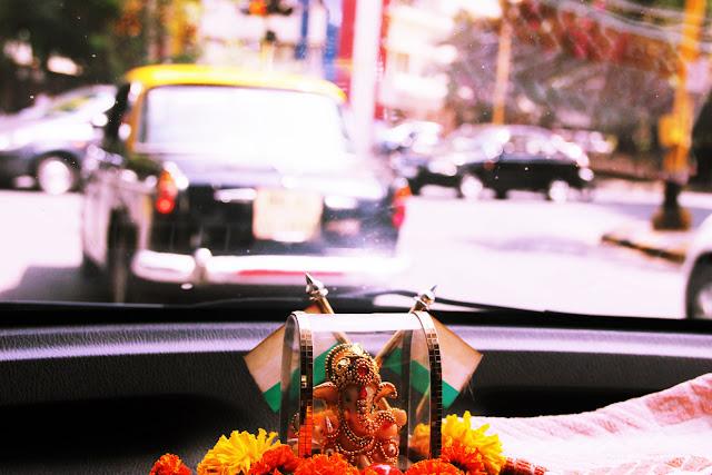 Lord Ganesh idol in a yellow taxi in Mumbai.