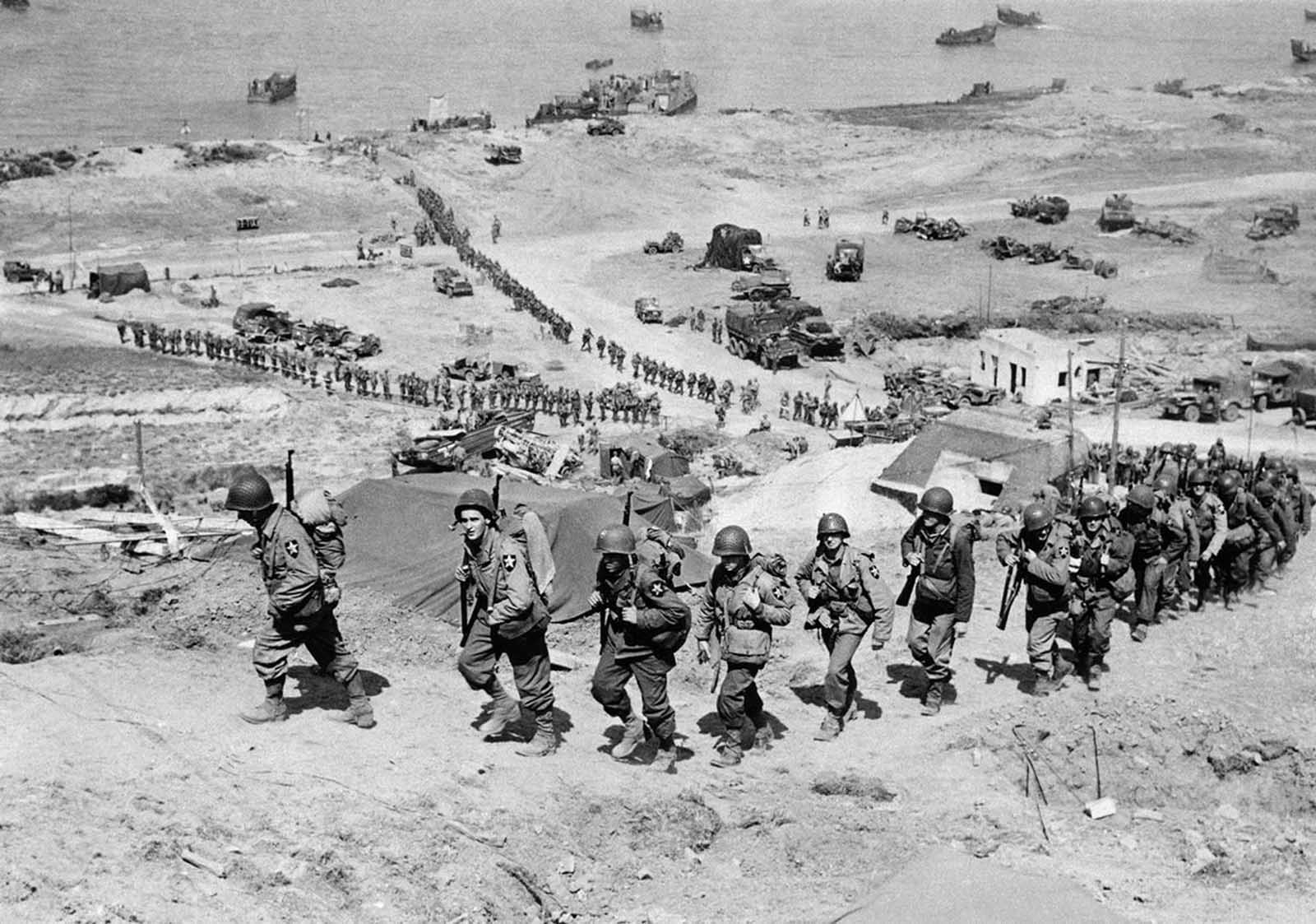 Reinforcements for initial allied invaders of France, long lines of troops and supply trucks begin their march on June 18, 1944, in Normandy.