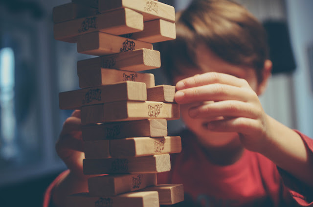A young white boy in a red shirt is about to pull out a Jenga piece from a tower.