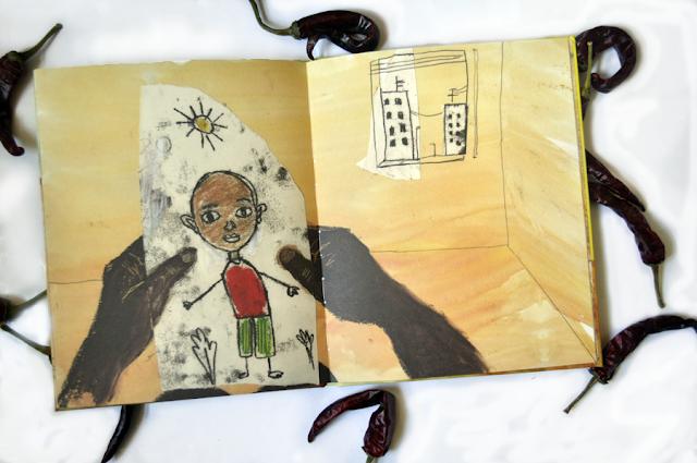 una manos adultas sostienen un dibujo infantil de un niño