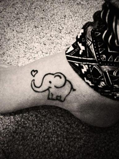 Um estilo cartoon elefante é ilustrada na utente de pé em tinta preta, com um coração no final de seu tronco esta tatuagem.