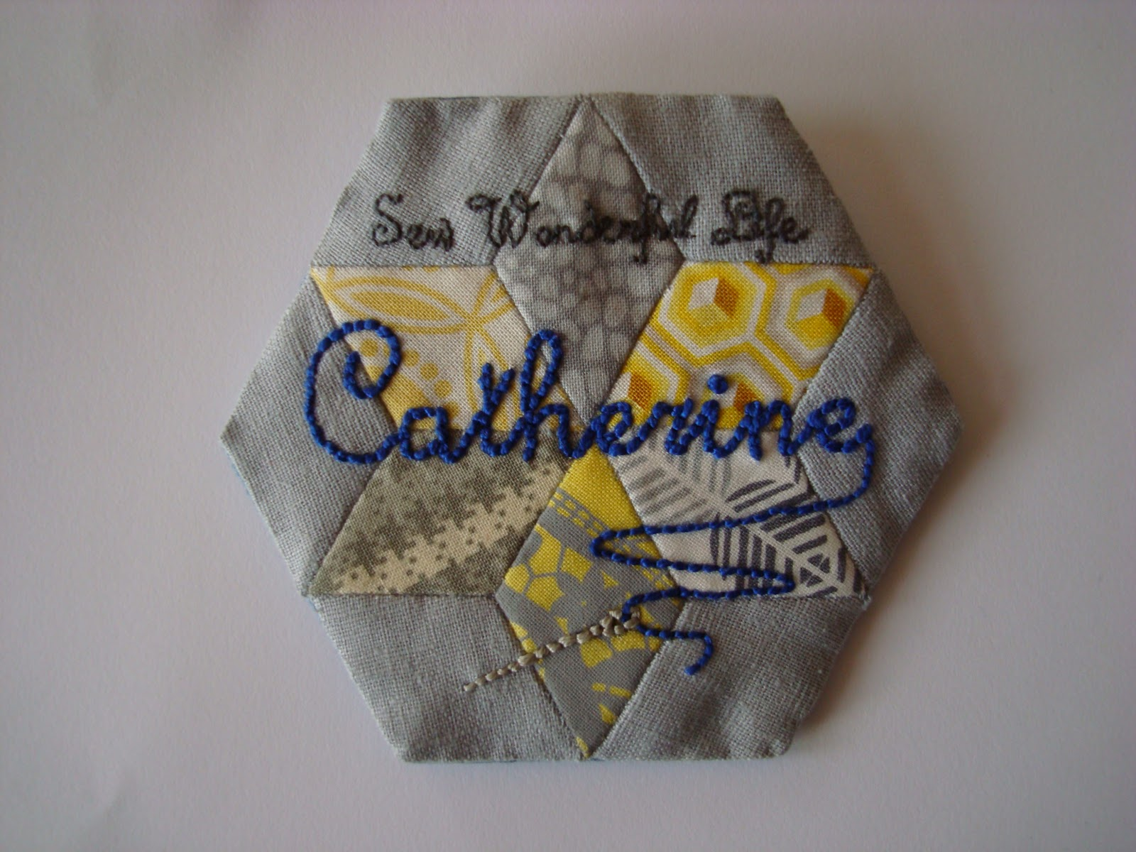 hexagon brooch made of kite shapes with Catherine embroidered across the middle