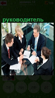 руководитель проводит совещание а столом с сотрудниками