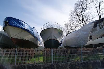 Sportboote stehen hinter einem Zaun aufgebockt auf einer Wiese. Das rechte Boot ist mit einer blauen Plane bedeckt