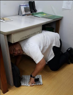 Usec Laguda taking cover under the office table