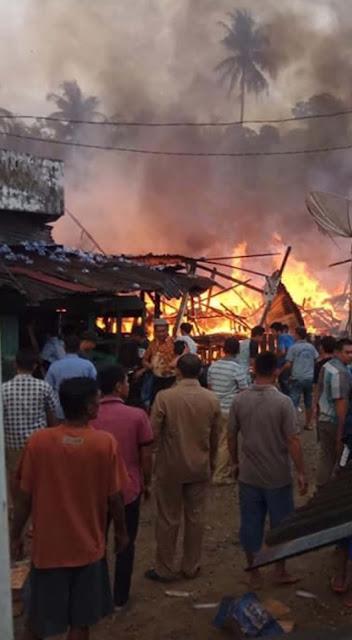Warga menyaksikan rumah peninggalan Raja Mandina yang terbakar.