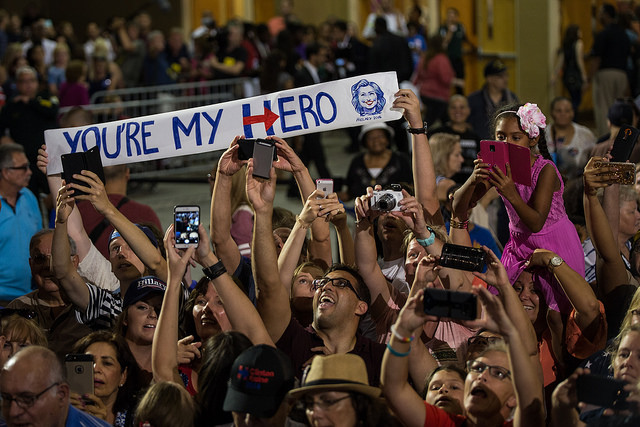 image of a cheering crowd at a Clinton-Kaine campaign event; some people are holding up a banner featuring Hillary's face and the words YOU'RE MY HERO, with H in hero her campaign logo; a few people over, a little Black girl in a purple dress taking a picture with her purple-covered tablet sits on (presumably) her mom's shoulders, and her mom is peering out from under the bottom of the girl's dress with a huge grin on her face