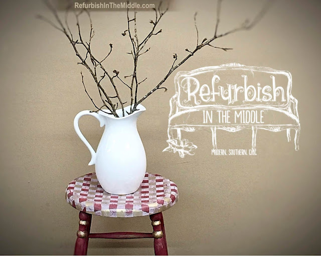 white pitcher with branches sitting on top of a red distressed tall chair accented with gingham checks