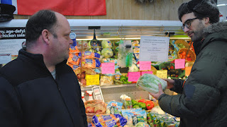Two men in produce section of grocery store