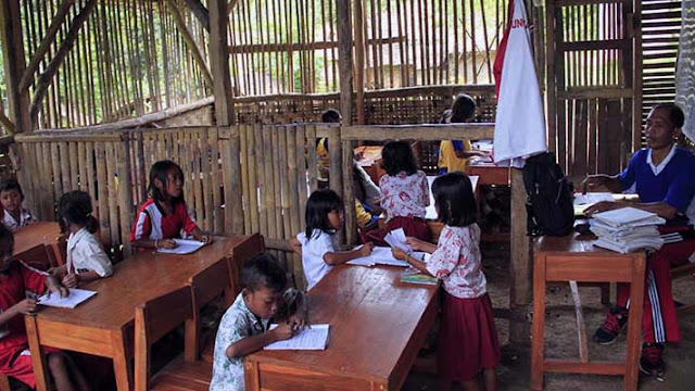 Seorang guru mengajar dua kelas sekaligus di ruangan terbuat dari bambu di SD Negeri Girijagabaya/Antara.