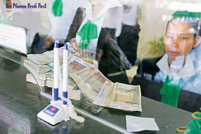 Banknotes lie stacked behind the counter of a Prasac Microfinance Institution branch in Kampong Speu province in December 2014. Hong Menea