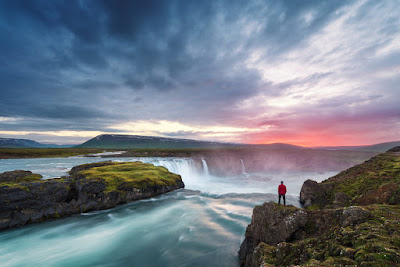 Man admiring the Diamond Circle's Godafoss waterfall at sunset