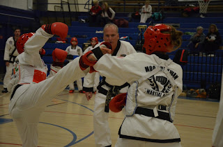 Black belt taekwondo woman performing a roundhouse kick while sparring