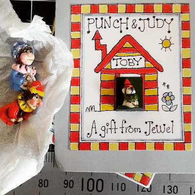 One-twelfth scale miniature Punch and Judy figures next to a card which reads 'Punch and Judy Toby A gift from Jewel'