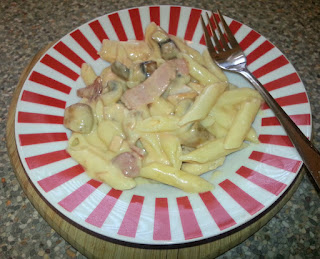 Chicken and bacon pasta in striped dish