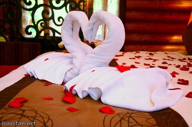 Two love swans shaped into a heart amidst rose petals on the bed