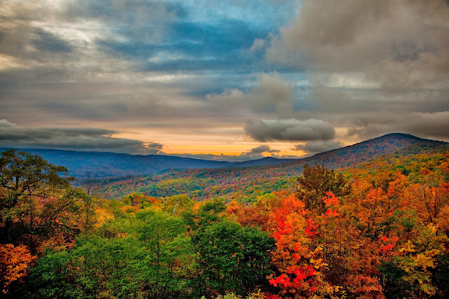 Vibrant fall colors across the trees in upon the mountain tops glow in the evening sun. The clouds above highlight the last glimpses of the autumn sun at the end of the day. Picture Height: 3744 pixels | Picture Width: 5616 pixels | Lens Aperture: f/4 | Image Exposure Time: 1/30 sec | Lens Focal Length mm: 24 mm | Photo Exposure Value: 1.33 EV | Camera Model: Canon EOS 5D Mark II | Photo White Balance: 0 | Color Space: sRGB |