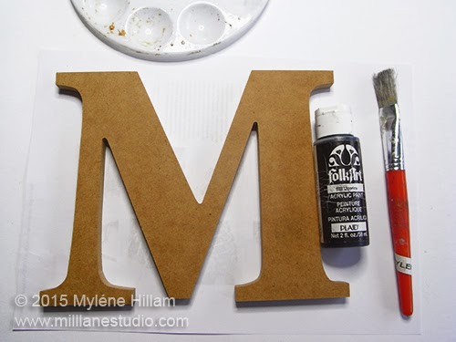 Preparing to paint the wooden letter with Folk Art black acrylic paint.