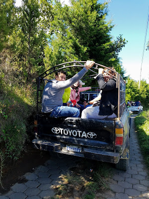 people riding in the back of a pickup truck in Guatemala