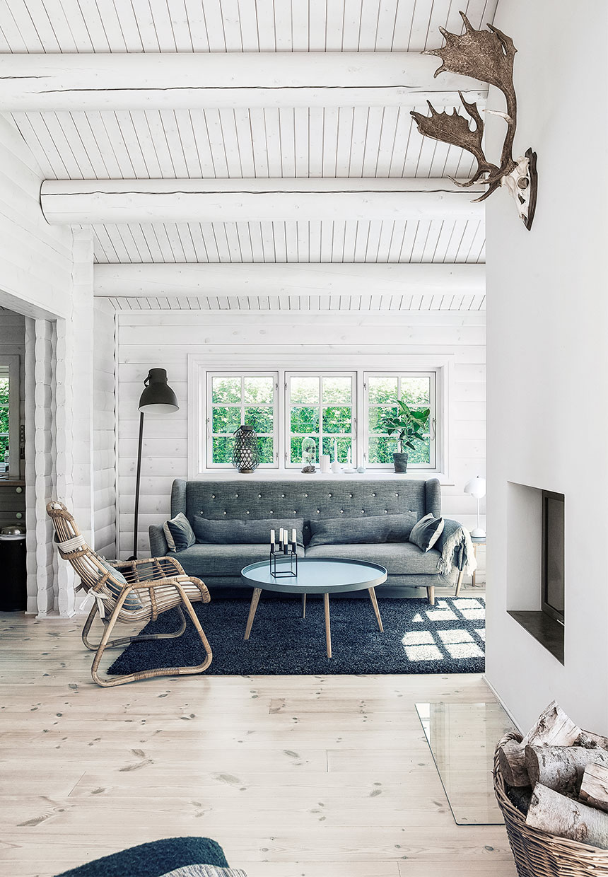 Inside of a log cabin scandinavian interior design black and white gray sofa