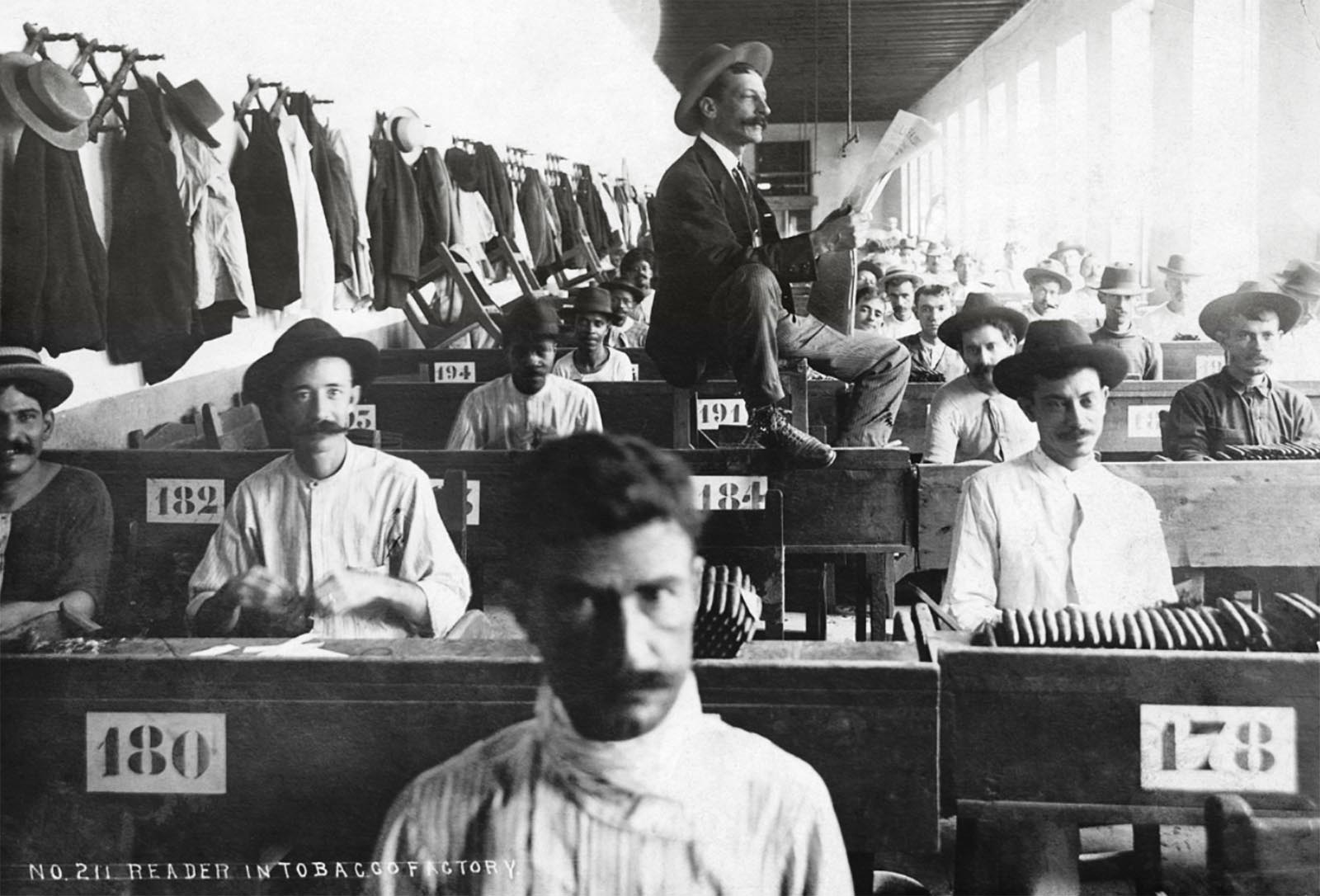 A hired reader reads to cigar makers hard at work in Cuban cigar factory, ca. 1900-1910