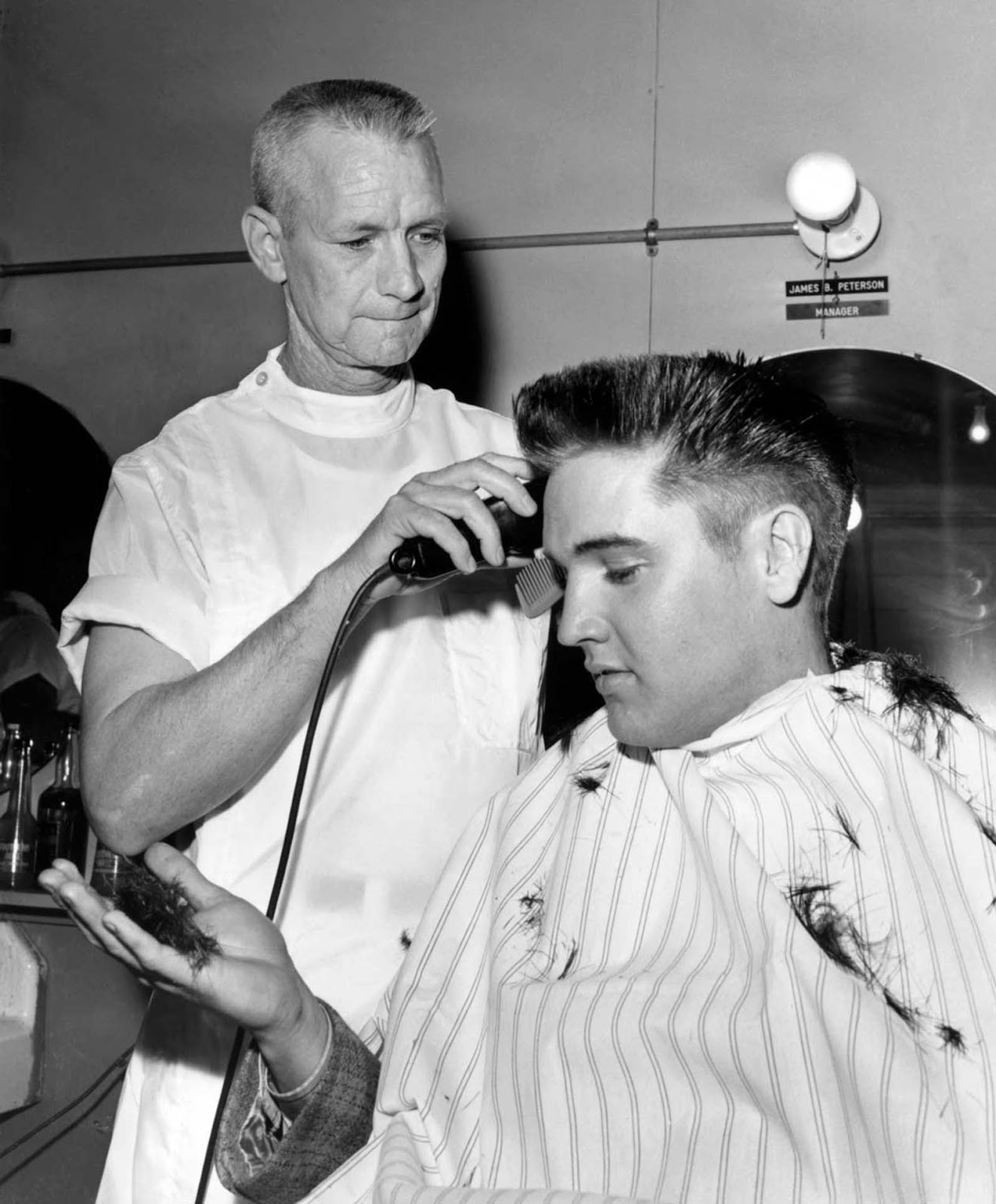 Elvis Presley receives a crew cut on his first full day as a member of the U. S. Army.
