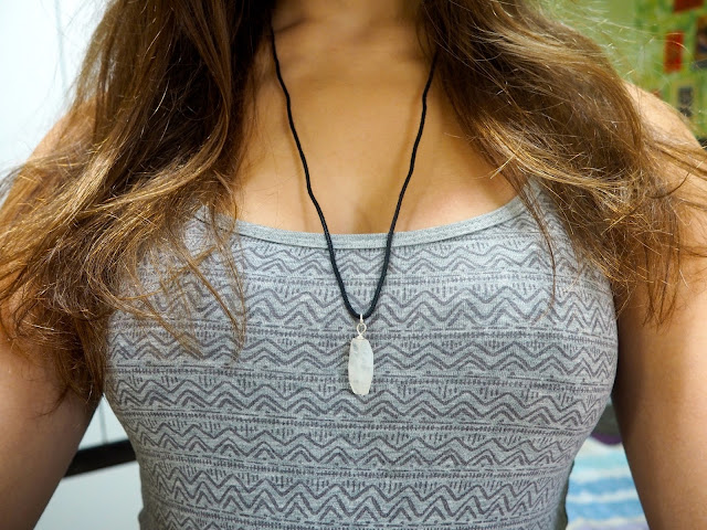 Slouching Around - outfit close up of grey geometric print pattern and white crystal on rope necklace