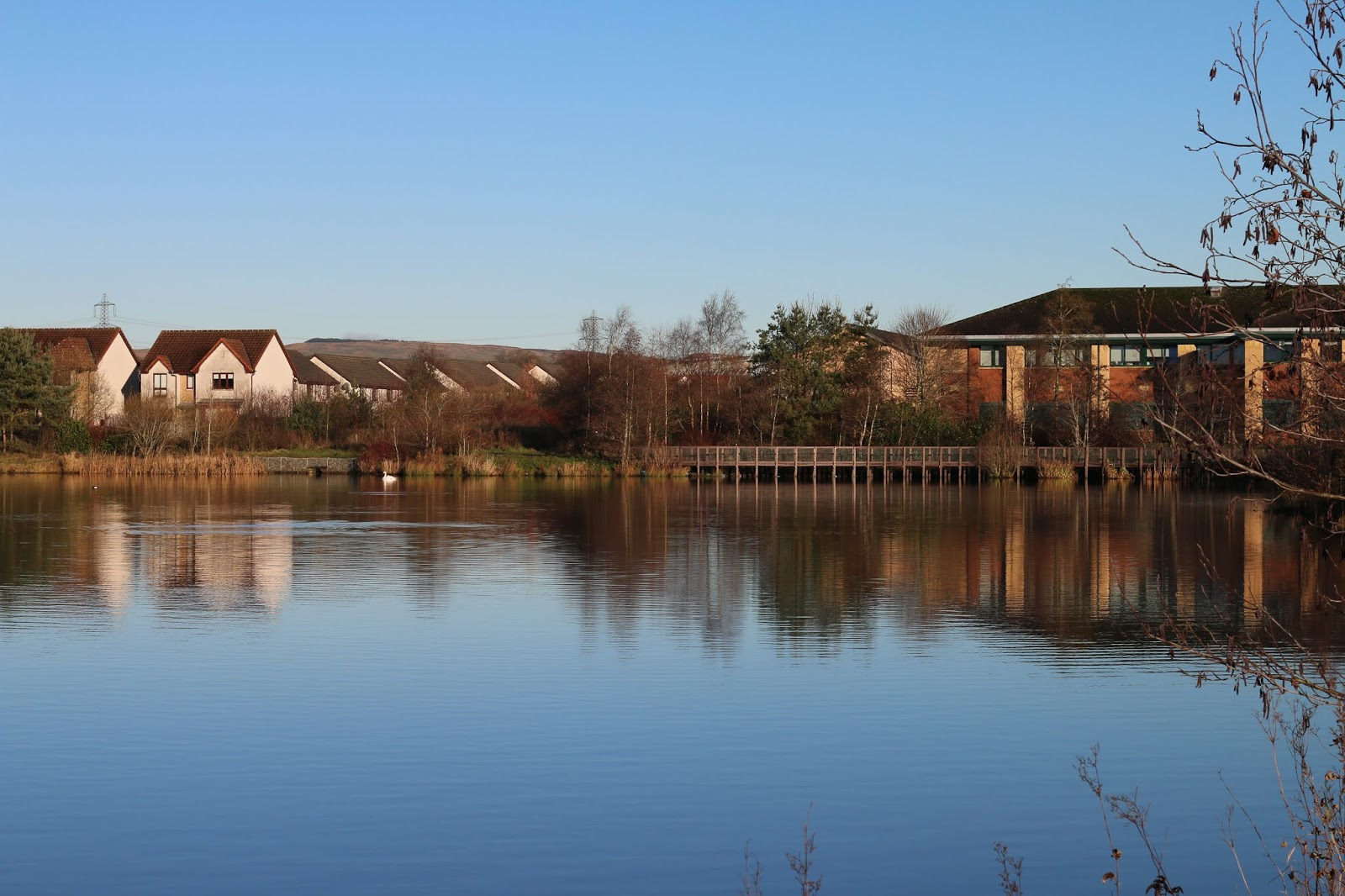 a landscape photo of broadwood lock with blue skies and deep blue water with houses in the background