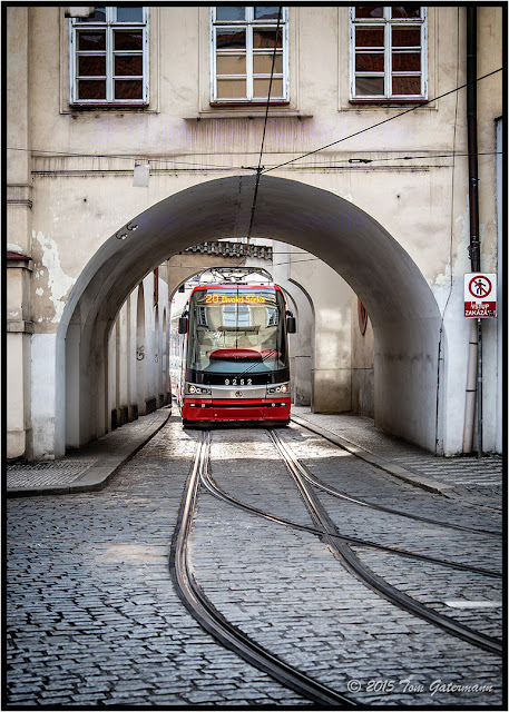Tram 9252 rolls through an archway under a building in Lesser Town Prague.