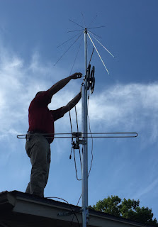 Chris on roof installing antenna on mast.