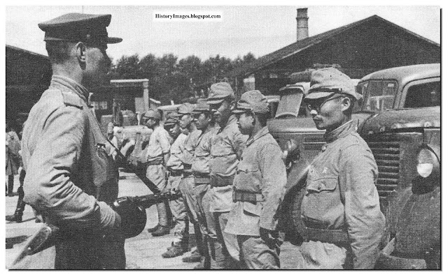 A Russian soldier stands guard over Japanese POWs