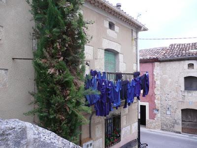 Balcón en un pueblo en el que hay colgados de la cuerda una serie de monos de trabajo azules.