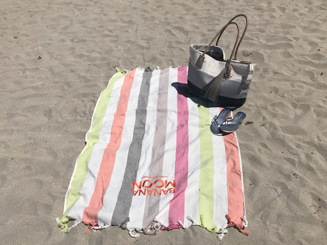 Beach towel, silver flip flops and large beach bag on a beach in Majorca