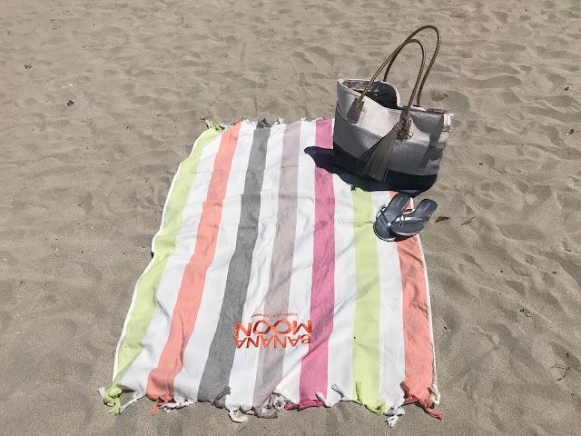 Beach towel, silver flip flops and large beach bag on a beach in Majorca