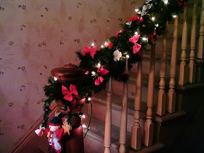 A staircase in an old Victorian home decorated with with garland, lights and bows.