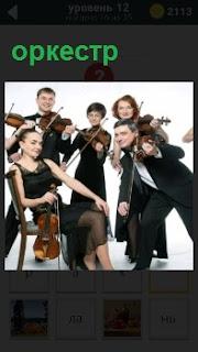 Несколько артистов из оркестра с инструментами для исполнения музыки, одна сидит, другие на ногах танцуют