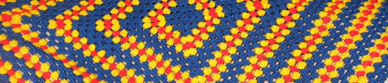close up of 'granny blanket' in Crows colours of blue, red and yellow.