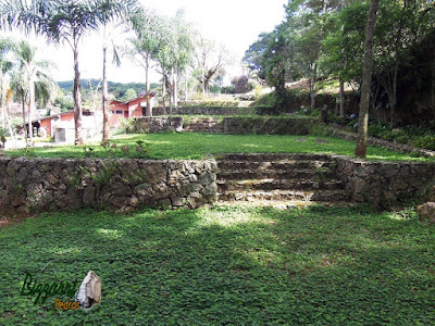 Escada de pedra no jardim com pedra rachão, um tipo de pedra rústica que é a sobra de pedra quando está tirando a pedra paralelepípedo ou a pedra rachão, com os muros de pedra em área de lazer de condomínio em Atibaia-SP.