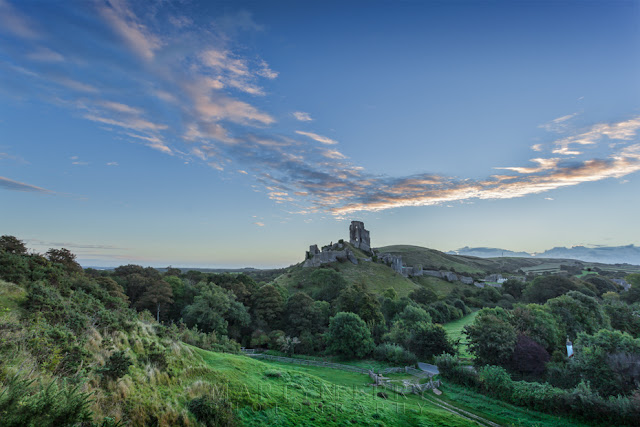Early morning image of Corfe Castle in Dorset with a line of clouds above.