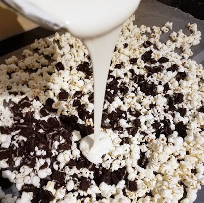 pouring melted white chocolate over bowl of cookie pieces and popcorn