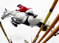 Bir jokey atıyla engellerin üzerinden hızla atlarken havada çekilmiş fotoğrafı