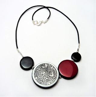collier graphique et contemporain rouge et noir avec dessins de la série tf1 insoupçonnable