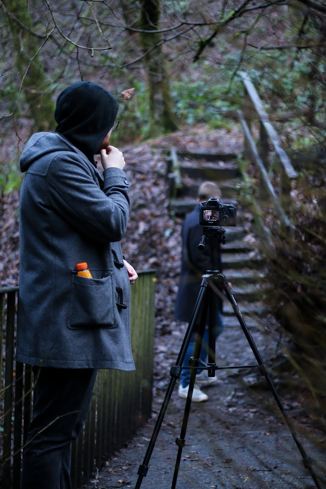 two men standing, one behind a camera filming the other walk down some stairs in Cumberland glen