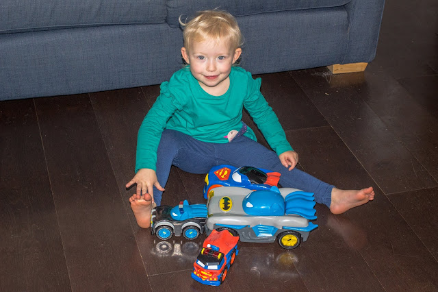 A preschooler with the Herodrive review toys in front of her