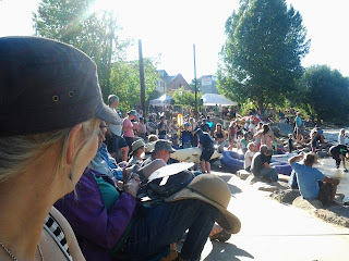 Lots of spectators sitting along the river bank watching the whitewater festival on a sunny day.