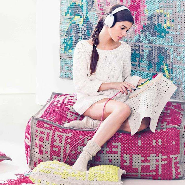 Girl listening to music sat on chunky cross stitch floor cushion