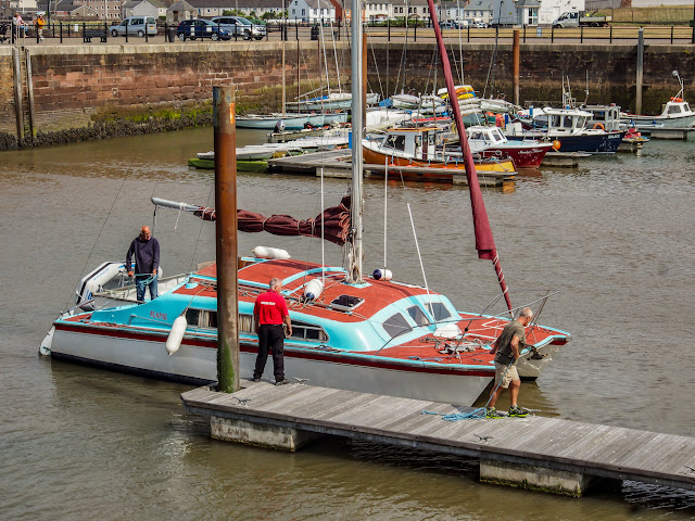 Photo of Phil (right) helping to moor up the cat when it returned to Maryport Marina