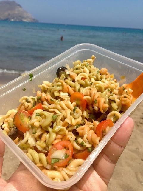 Ensalada de pasta con albahaca, aceitunas, tomate y cebolla en la playa